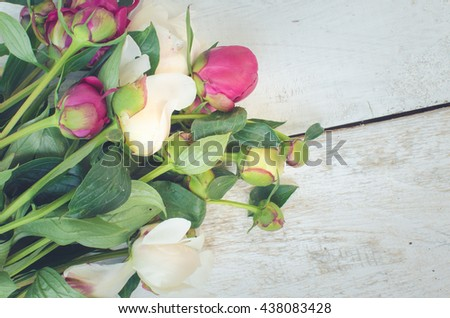 Peony background. Fuchsia, pink and white peonies on white wooden table with place for text. Spring flower. Happy Mothers Day. Mother's Day greetings card. Mothers Day gift. Copy space. Toned image. - stock photo