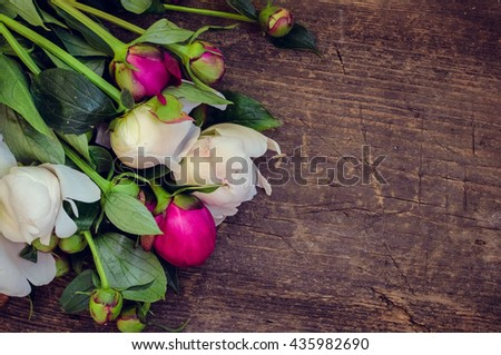 Peony background. Fuchsia, pink and white peonies on wooden table with place for text. Spring flowers peonies. Happy Mothers Day. Mother's Day greetings card. Mothers Day gift. Copy space. - stock photo