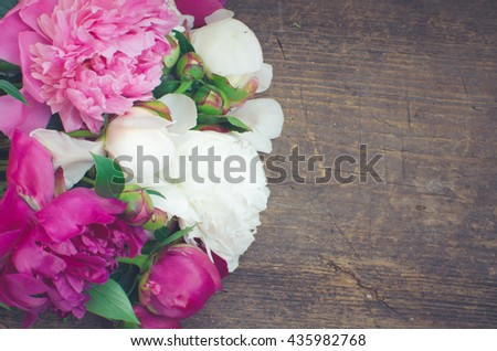 Peony background. Fuchsia, pink and white peonies on wooden table with place for text. Spring flower peon. Happy Mothers Day. Mother's Day greetings card. Mothers Day gift. Copy space. Toned image. - stock photo