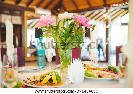 peony bouquet in vase and fish plates on table