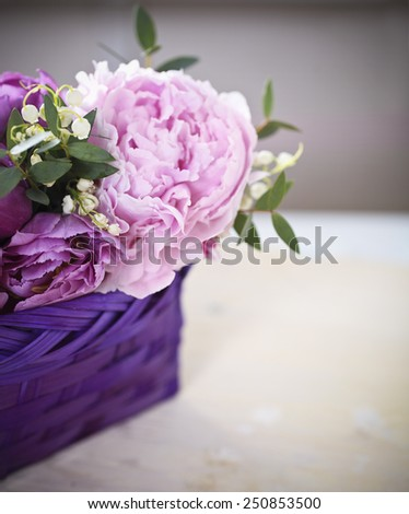 Peony flower, tulips and lilies of the valley and  on the wooden background in violet basket - stock photo