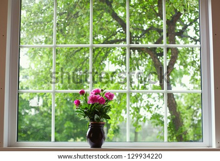 peony flowers on widnow-sill - stock photo