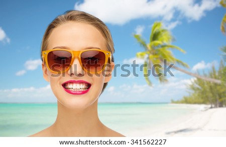 people, accessory, summer vacation, travel and fashion concept - smiling young woman in sunglasses with pink lipstick on lips over tropical beach with palm background