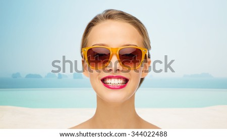 people, accessory, vacation, travel and fashion concept - smiling young woman in sunglasses with pink lipstick on lips over infinity edge pool background - stock photo