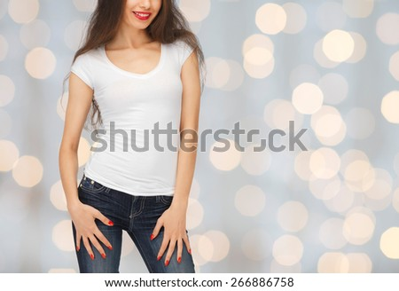 people, advertisement, holidays and t-shirt design concept - close up of smiling young woman in blank white t-shirt over lights background - stock photo