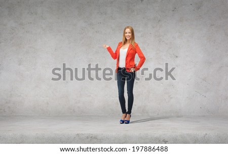 people, advertising and happiness concept - beautiful teenage girl in casual clothes on high heels holding something on her palm