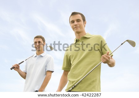 People against blue sky with golf clubs (focus on person in the back)