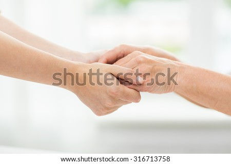 people, age, family, care and support concept - close up of senior woman and young woman holding hands - stock photo