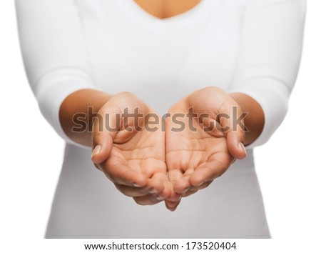 people and advertisement concept - close up of womans cupped hands showing something - stock photo