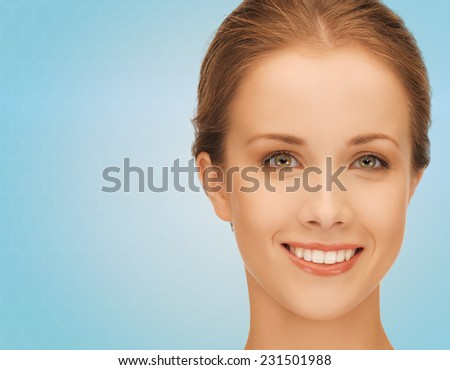 people and beauty concept - beautiful smiling young woman over blue background - stock photo