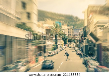 People and cars moving around on Longstreet in Cape Town downtown before sunset  - Commuters walking in south african business district - Radial zoom defocusing on a vintage filtered look - stock photo
