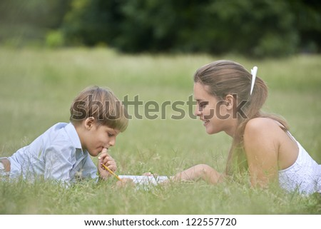 People and education, mother helping child with homework, lying on grass and reading book at park. Medium shot - stock photo