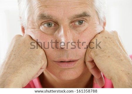 people and emotions, portrait of depressed senior Caucasian man,  with hands on chin