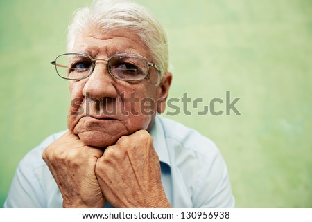 people and emotions, portrait of depressed senior hispanic man with glasses looking at camera, leaning with hands on chin. Copy space - stock photo