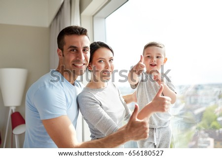 people and family concept - happy mother, father and little son showing thumbs up at home window