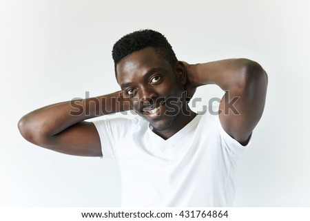 People and lifestyle concept. Close up of handsome young dark-skinned man wearing white T-shirt, looking at the camera with happy pleased expression on his face, holding both hands behind his head - stock photo