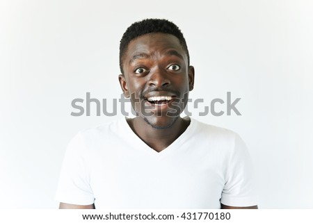 People and lifestyle concept. Happy excited African student in casual white T-shirt looking at the camera in excitement, passing final exams at university with excellent marks. Success and achievement - stock photo