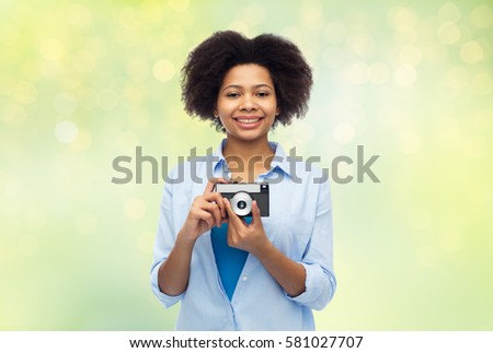 people and photography portrait concept - happy african american young woman with film camera over summer green lights background