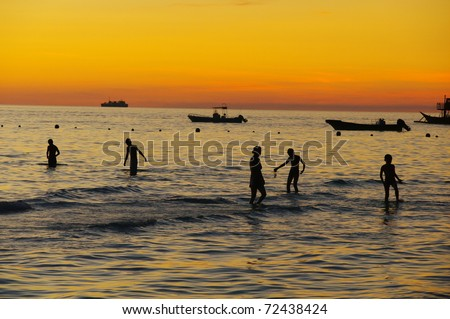 people and sea under sunset - stock photo