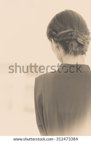 People and solitude concept. Alone woman looking through window waiting back view indoor