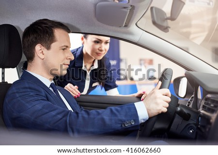 people and technology concept - salesman showing new car to male customer in automobile center - stock photo