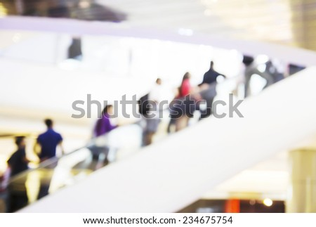 People are going up the escalator in the shopping mall. Blur background. - stock photo