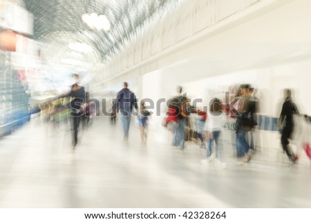 People are rushing in shopping center. A zoom lens was used to make the people appear blurry. - stock photo