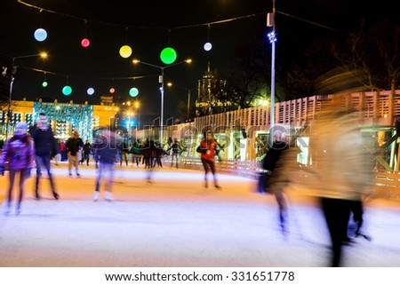 People are skating in the park on winter skating rink - stock photo