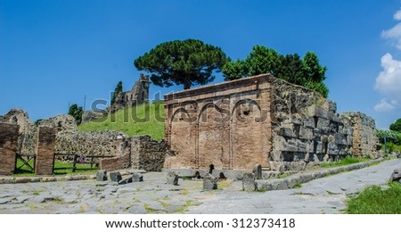 people are strolling through one of the few maintained gardens inside of the pompeii ruins complex near italian naples. - stock photo