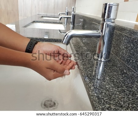 People are washing their hands from the faucet.Water from the tap is stopping.