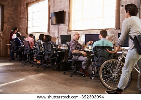 People Arriving For Work In Modern Design Office - stock photo