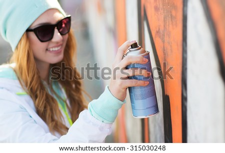people, art, creativity and youth culture concept - close up of young woman or teenage girl in sunglasses drawing graffiti with spray paint on street wall - stock photo
