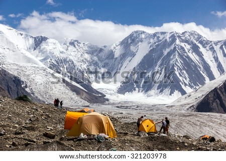 People Assembling Bivouac Group of Alpine Climbers Working on setting up Camping Tents at Side Rocky Moraine of Glacier and High Altitude Mountain Range on Background - stock photo