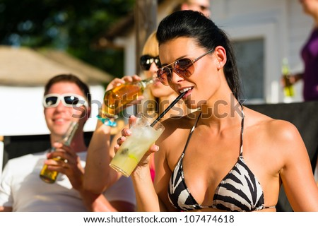 People at beach drinking having a party, woman or girl in front drinking cocktail - stock photo