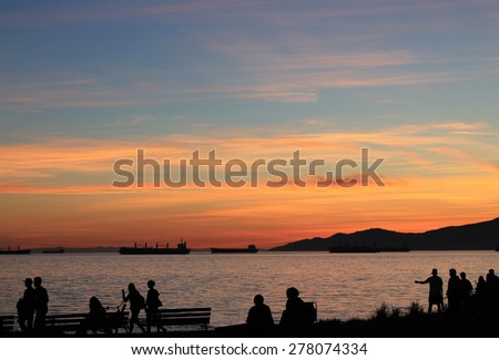 People at coast beach on evening summer at sunset sky with barge in background  - stock photo