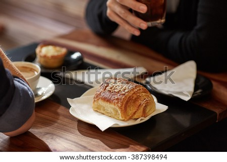 People at modern cafe table with coffee and croissants - stock photo