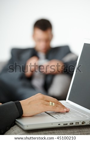 People at office. Businesswoman writing notes to laptop computer. Focus on typing  female hand. - stock photo