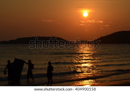 People at the beach in the evening: Silhouette.