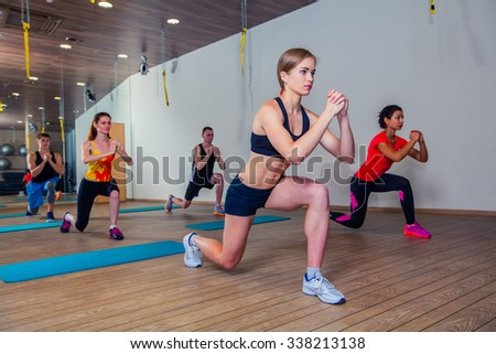 People at the health club with personal trainer, learning the correct form. - stock photo
