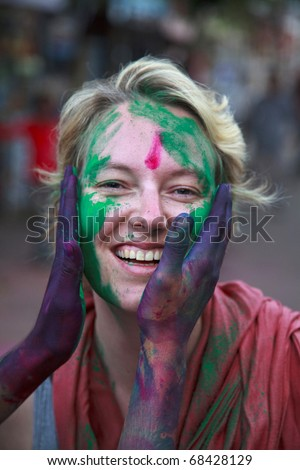 People at the holi festival in India. Holi, or Holli,is a spring festival celebrated by Hindus, Sikhs and others. People throwing coloured powder and coloured water at each other. - stock photo