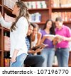 People at the library and woman looking for a book - stock photo
