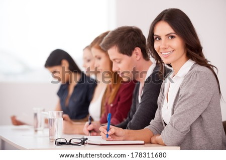 People at the seminar. Attractive young woman smiling at camera while sitting together with another people at the table - stock photo