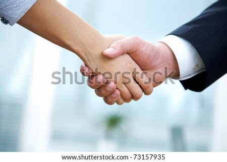 People at work: man and woman hand shaking at a meeting - stock photo