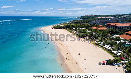 People bathing in the sun, swiming and playing games on the beach. Tourists on the sand beach of Nusa Dua, Bali, Indonesia.