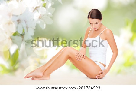 people, beauty and body care concept - beautiful woman in cotton underwear touching her hips over green natural cherry blossom background