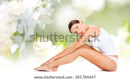 people, beauty and body care concept - beautiful woman in cotton underwear touching legs over green natural cherry blossom background