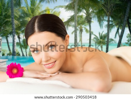 people, beauty and body care concept - happy beautiful woman lying on massage desk at spa resort over sea and pool on tropical beach with palms background