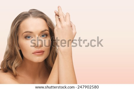 people, beauty, body and skin care concept - beautiful woman face and hands over pink background - stock photo