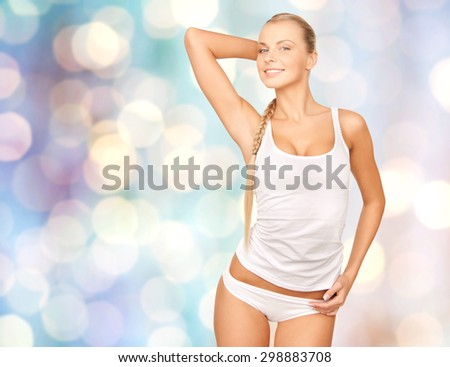 people, beauty, body care and fashion concept - happy beautiful young woman in cotton underwear posing over blue holidays lights background - stock photo