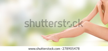 people, beauty, health and body care concept - close up of naked woman legs over green background